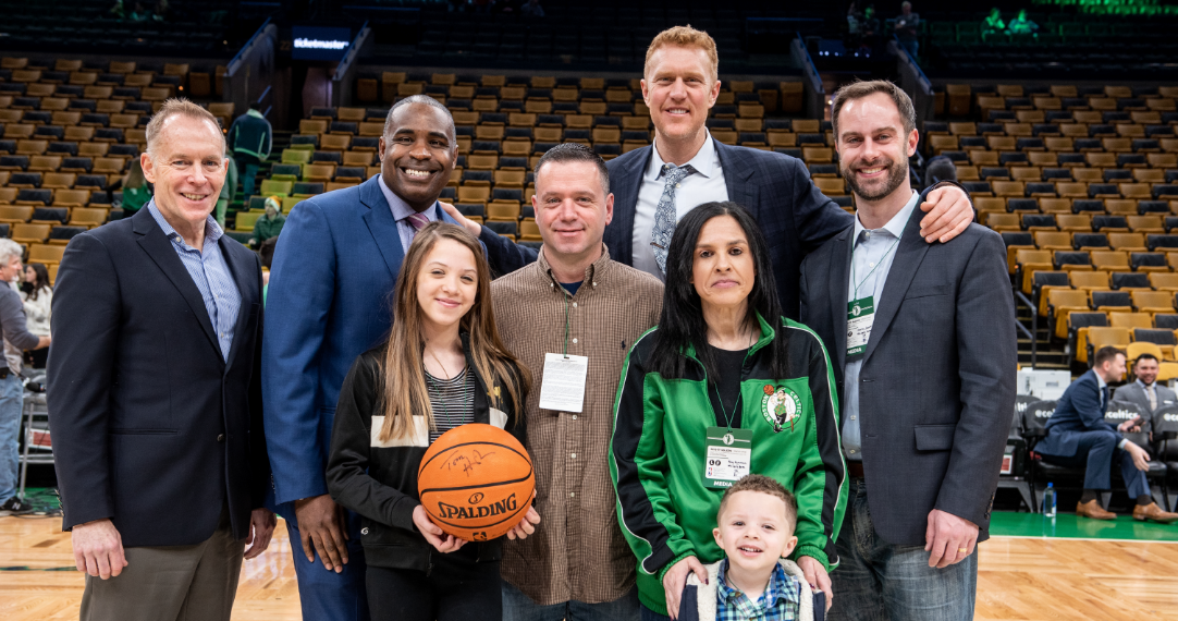 Happy family with Celtics players and a basketball