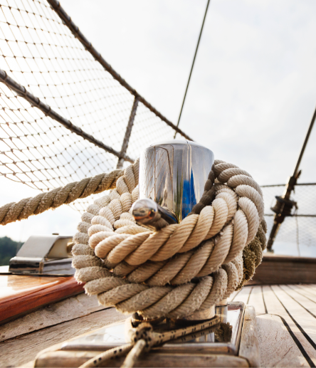 A thick tan rope wrapped around a silver bitt on the wooden deck of a sailboat